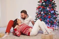 有说谎在地板上的女孩的人在新年圣诞树 免版税库存照片