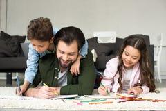 有说谎在地毯和画与上色的逗人喜爱的孩子的愉快的父亲 免版税库存照片