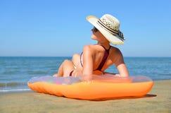 有说谎在海滩的可膨胀的床垫的帽子的白种人女孩 库存图片