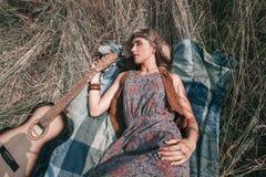 有说谎在草的吉他的年轻嬉皮妇女 免版税图库摄影