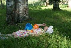 有说谎在草的玩具的小女孩在森林里 免版税库存图片