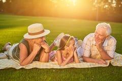 有说谎的孙女的祖父母户外 免版税图库摄影