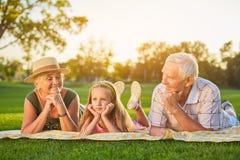 有说谎的祖父母的女孩户外 免版税库存照片