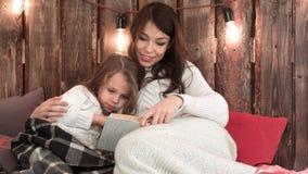 有读书和放松在一个舒适沙发的小女孩的妈妈在圣诞灯下 免版税库存图片