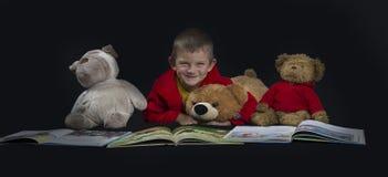 有读书的填充动物玩偶的滑稽的男孩在床时间前 免版税库存照片