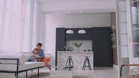 有读书的孩子的一个年轻母亲坐在房子的明亮的白色内部在客厅在 影视素材