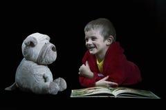 有读床时间的一条被充塞的狗的滑稽的男孩一本书在arti 免版税库存照片