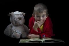 有读床时间的一条被充塞的狗的滑稽的男孩一本书 免版税库存图片