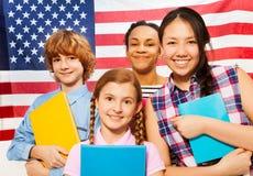 有课本的微笑的美国少年学生 免版税库存图片