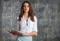 有课本的年轻聪明的俏丽的妇女在黑板附近 库存图片