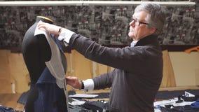 有调整物质样式的测量的磁带的成功的成熟裁缝对时装模特 缝合夹克的过程在 影视素材