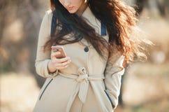 有调查智能手机的飞行头发的女孩 免版税库存照片