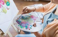 有调色刀绘画的艺术家在艺术演播室 库存照片