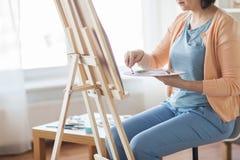 有调色刀绘画的艺术家在艺术演播室 免版税库存照片
