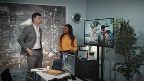有谈论录影编辑的片剂的混合的族种录影设计师在一个大屏幕上观看了 股票视频