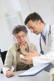 有谈论疗程的医生的年长夫人 免版税库存图片