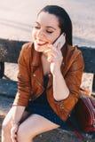 有谈话和笑的愉快的年轻女人在智能手机智能手机在城市公园坐长凳 库存图片