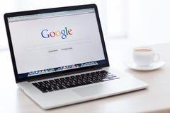 有谷歌主页的MacBook赞成视网膜在屏幕上站立  库存图片