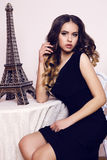 有豪华卷发的美丽的少妇在典雅的黑礼服 免版税图库摄影