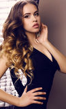 有豪华卷发的美丽的少妇在典雅的黑礼服 图库摄影