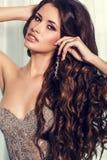 有豪华卷曲黑发的性感的女孩在典雅的米黄礼服 免版税库存图片