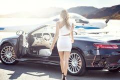 有豪华汽车和飞机的性感的妇女 库存照片