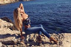 有豪华金发的性感的女孩在摆在海滩的牛仔裤 免版税库存图片