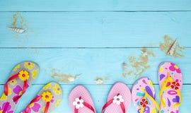 有贝壳和沙子的海滩鞋子在木背景,夏天休假概念 库存图片
