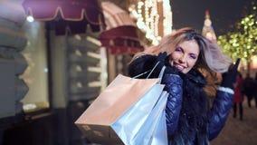 有购物带来的画象微笑的shopaholic妇女在照亮的圣诞灯背景 股票录像