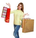 有购物袋偶然穿戴的摆在白色背景的演播室的牛仔裤和一件绿色毛线衣的女孩 库存图片