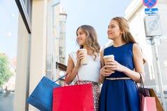 有购物袋和咖啡的愉快的妇女户外 免版税图库摄影