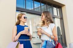 有购物袋和咖啡的愉快的妇女户外 免版税库存图片