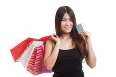有购物袋和空插件的年轻亚裔妇女 库存图片