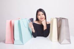 有购物袋和空插件的年轻亚裔妇女 免版税库存图片