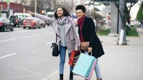 有购物袋的两名可爱的非裔美国人的妇女要求出租车,当回来从购物中心销售时 免版税库存图片