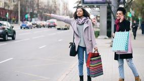 有购物袋的两名可爱的非裔美国人的妇女要求出租车,当回来从购物中心销售时 库存图片