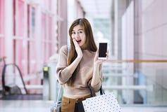 有购物袋的亚裔女孩使用智能手机 免版税库存图片