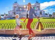 有购物袋的享受散步的母亲和孩子 免版税库存照片