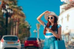 有购物袋的夏天寻找出租汽车的女孩和智能手机 免版税库存照片
