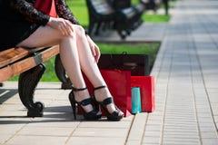 有购物袋的妇女坐公园长椅 免版税库存照片