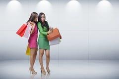 有购物袋的惊奇的两个亚洲人妇女,当看在smar时 库存照片