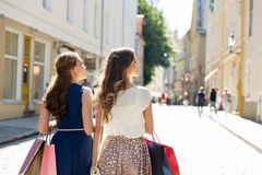 有购物袋的愉快的妇女在城市街道上 免版税库存照片
