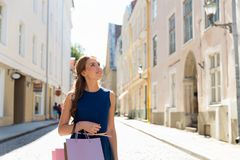 有购物袋的愉快的妇女在城市街道上 免版税图库摄影