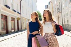 有购物袋的愉快的妇女在城市街道上 免版税库存图片