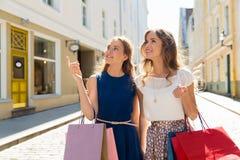 有购物袋的愉快的妇女在城市 免版税库存照片