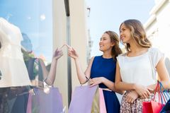有购物袋的愉快的妇女在店面 免版税图库摄影