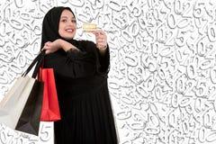 有购物袋的愉快的常设回教妇女和与假日例证的信用卡 免版税图库摄影