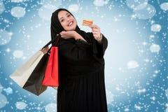 有购物袋的愉快的常设回教妇女和与假日例证的信用卡 库存照片