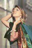 有购物袋的愉快的年轻时尚妇女走在购物中心的 库存照片