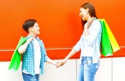 有购物袋的愉快的微笑的母亲和儿子孩子获得乐趣 库存照片